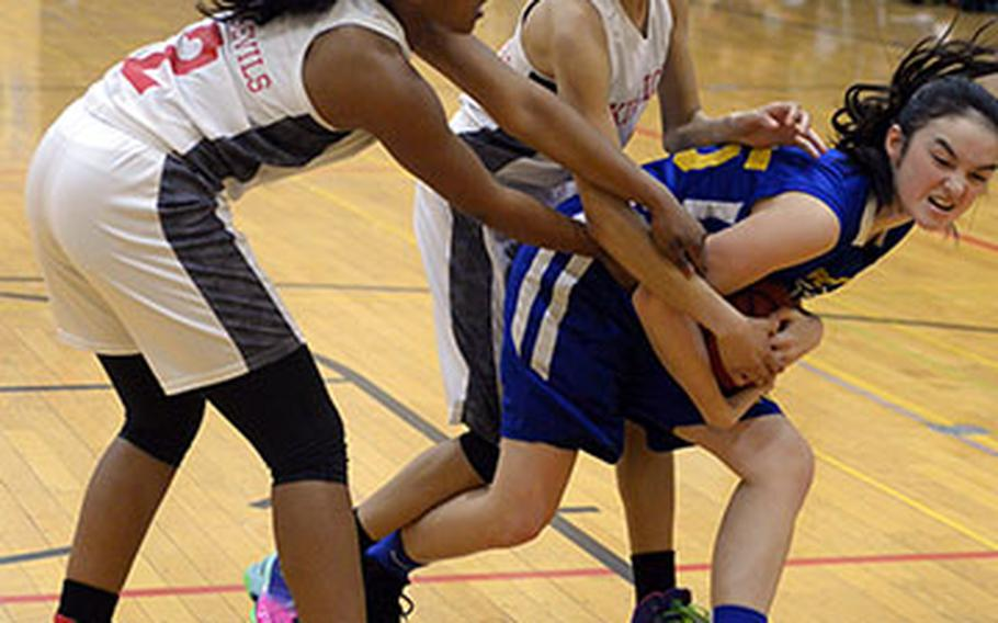 Gimme that ball! Yokota's Emily Taynton tries to keep the ball away from Nile C. Kinnnick's Jade McGinnis and Ernestina Roberts during Thursday's pool play game in the 2nd American School In Japan Kanto Classic Basketball Tournament. The Panther routed the Red Devils 32-11.