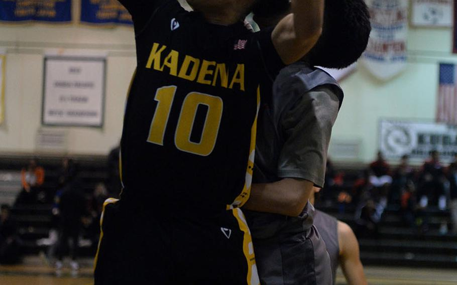 Kadena's James Laney snags a rebound in front of Nile C. Kinnick's Rashad Rapada during Monday's semifinal game in the Far East Boys Division I Basketball Tournament. The Red Devils won 88-76 to reach their first final since 2002.