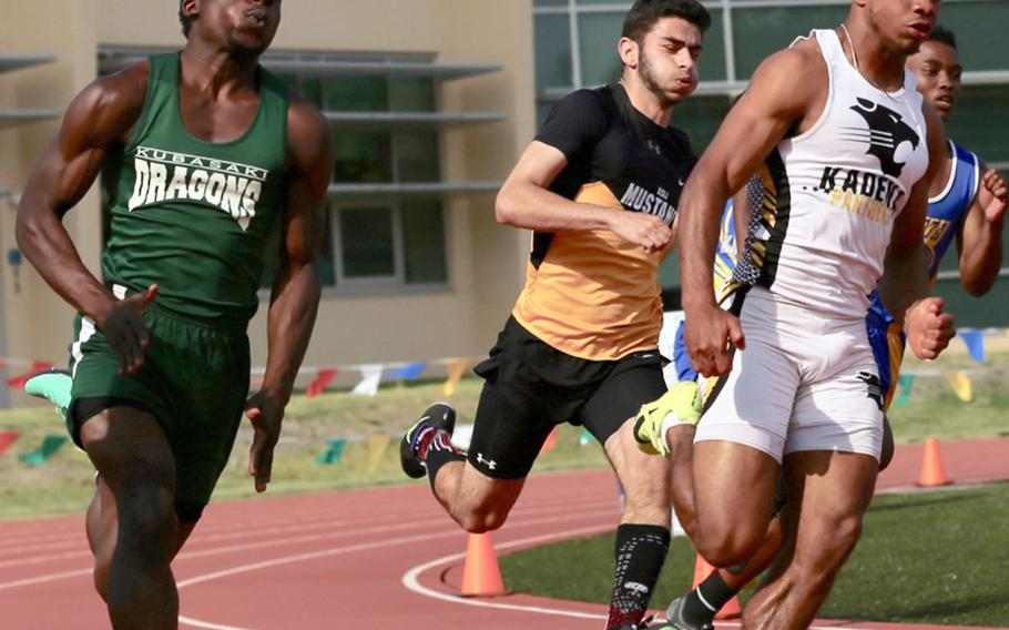Kadena's Eric McCarter and Kubasaki's Vincent Hill lead the pack around the far turn in Monday's boys 200 preliminary run in the Far East track and field meet. McCarter won in 22.19 seconds.