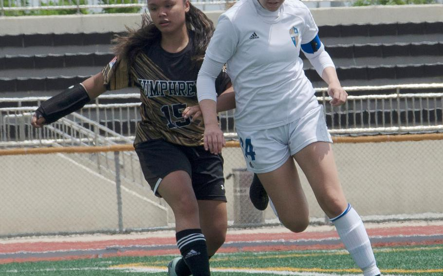 Yokota's Caleigh Garcia and Humphreys' Krystal Duenas battle for the ball during Monday's pool play match in the Far East Division II girls soccer tournament. Garcia scored eight goals in three matches to run her total to 40 this season. Yokota beat Humphreys 3-1.