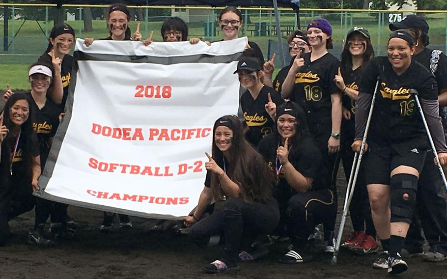 Banner time! Robert D. Edgren players gather round the Far East Division II softball tournament banner after beating Daegu 5-2 in the tournament final.
