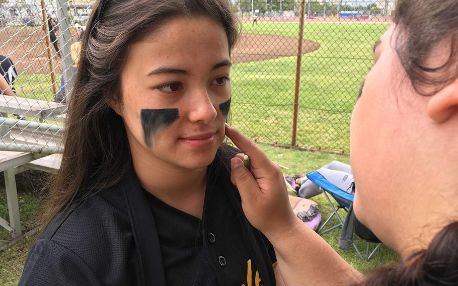Robert D. Edgren senior right-hander and Far East Division II Softball Tournament MVP Brittany Crown gets an eyeblack touchup before going out to fan 14 batters as the Eagles beat Daegu 5-2 in the tournament final.