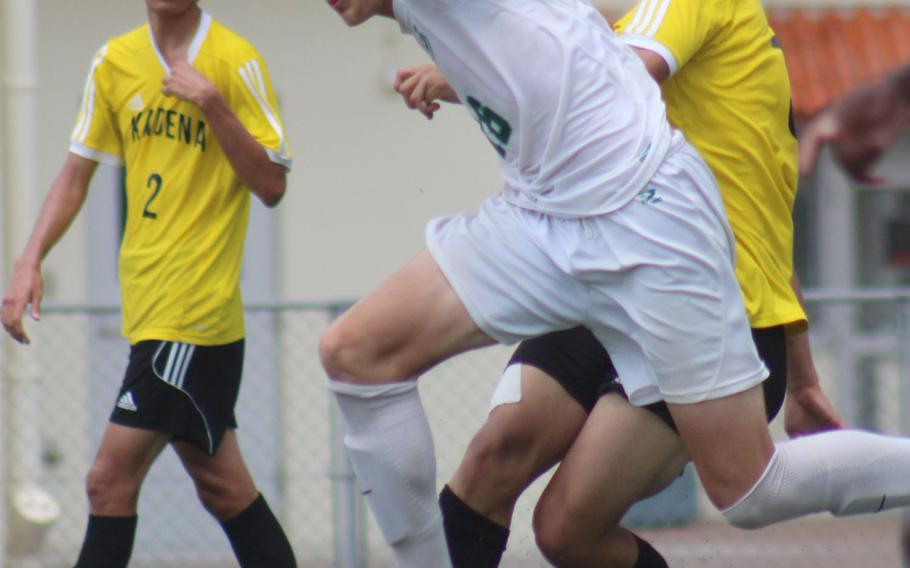 Kubasaki's Judge Morgan stumbles between Kadena defenders during Wednesday's final in the Far East Division I boys soccer tournament. The Dragons pulled away in the second half for a 4-0 win.
