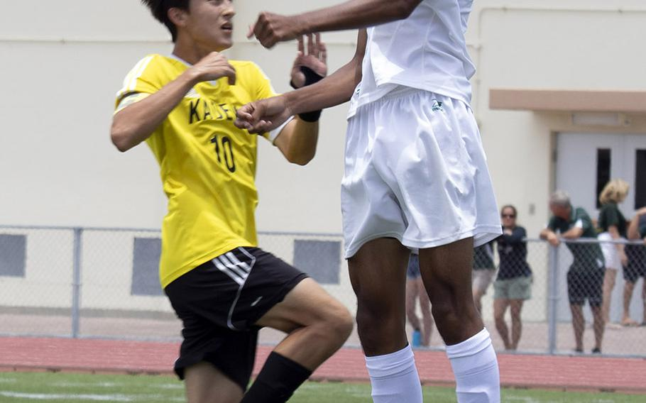 Kubasaki's Ilijah Washington heads the ball over Kadena's Kian Smith during Wednesday's final in the Far East Division I boys soccer tournament. The Dragons pulled away in the second half for a 4-0 win.