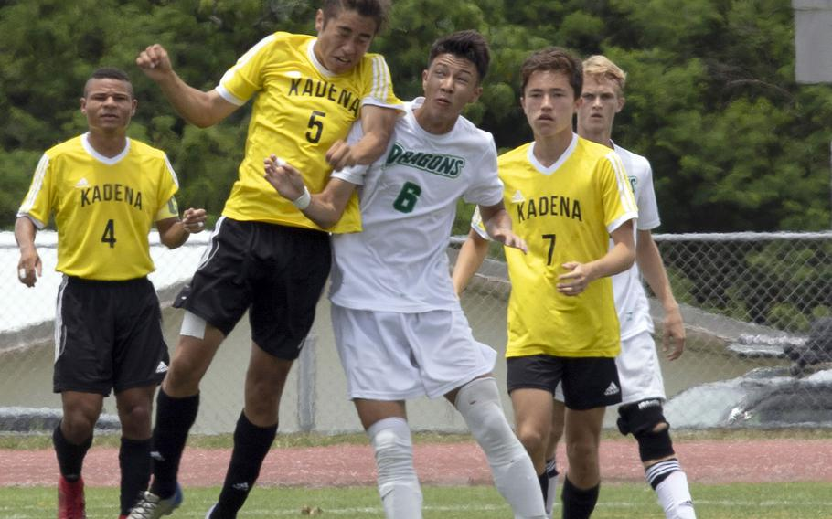 Kadena's Eric Fletcher heads the ball out of Kubasaki's Noah Hayes' way during Wednesday's final in the Far East Division I boys soccer tournament. The Dragons pulled away in the second half for a 4-0 win.