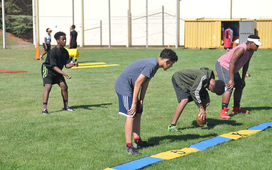 Baumholder players run through a practice snap in a preseason football session at Baumholder High School. The Bucs will play six-man football this fall after years of 11-man ball, requiring coaches and players alike to quickly grasp a new set of rules and strategies.
