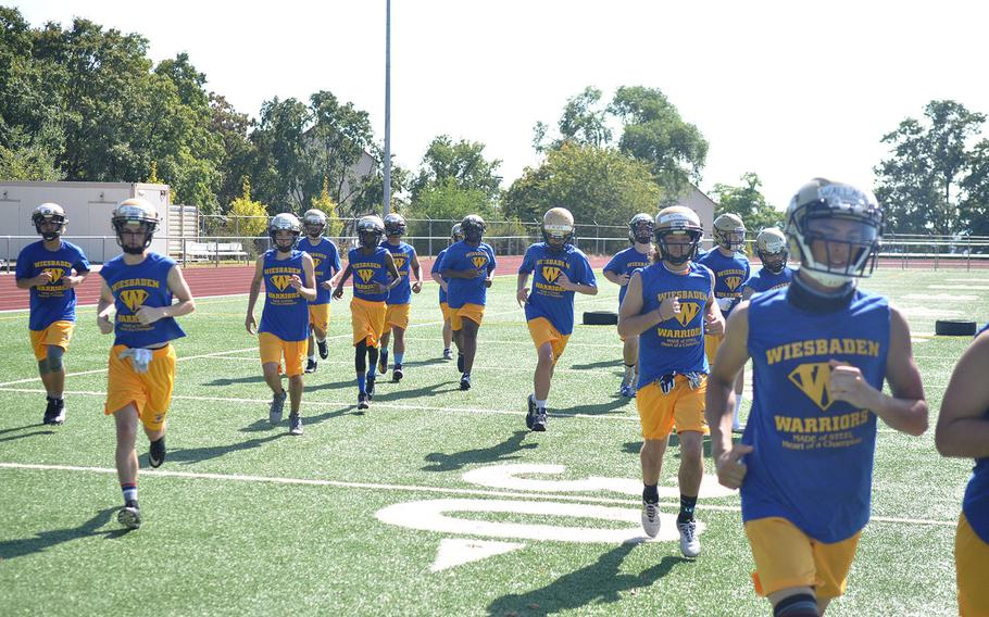 Wiesbaden football players jog off the field for a water break in the midst of a hot August practice session. The Warriors are looking to get back to the European title game after a semifinal loss last season.