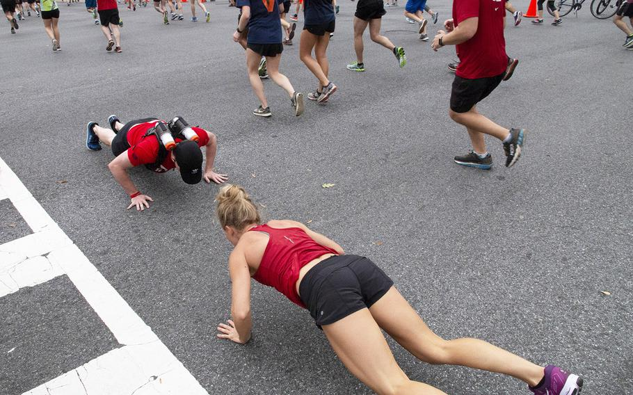 Devin Ruic of Arlington, Va., left, running for Team Red, White and Blue, stops to do some pushups with Gretchen Apgar during the Army Ten-Miler in Washington, D.C., Oct. 7, 2018.