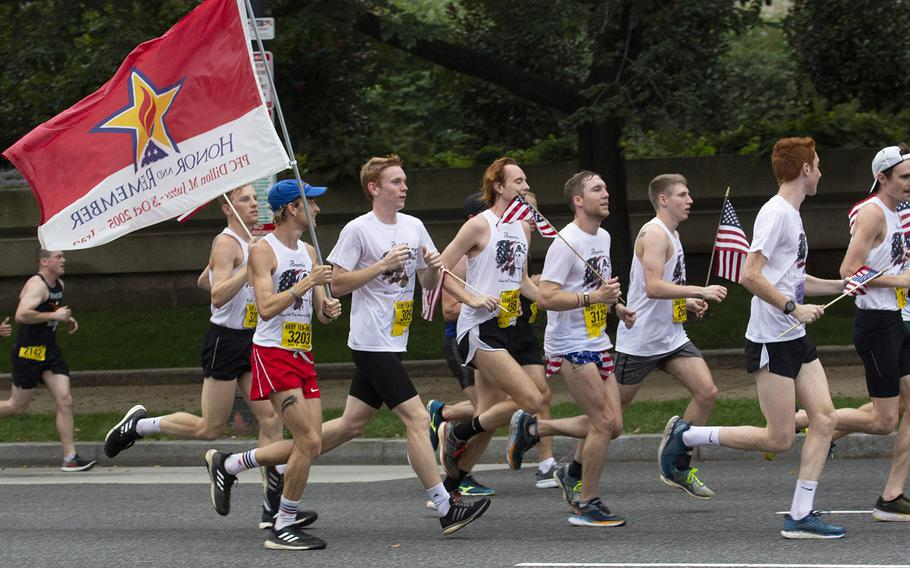 Hunter Jutras carries a flag a flag honoring his older brother Pfc. Dillon Jutras, who was killed in Iraq in 2005, during the Army Ten-Miler in Washington, D.C., Oct. 7, 2018.