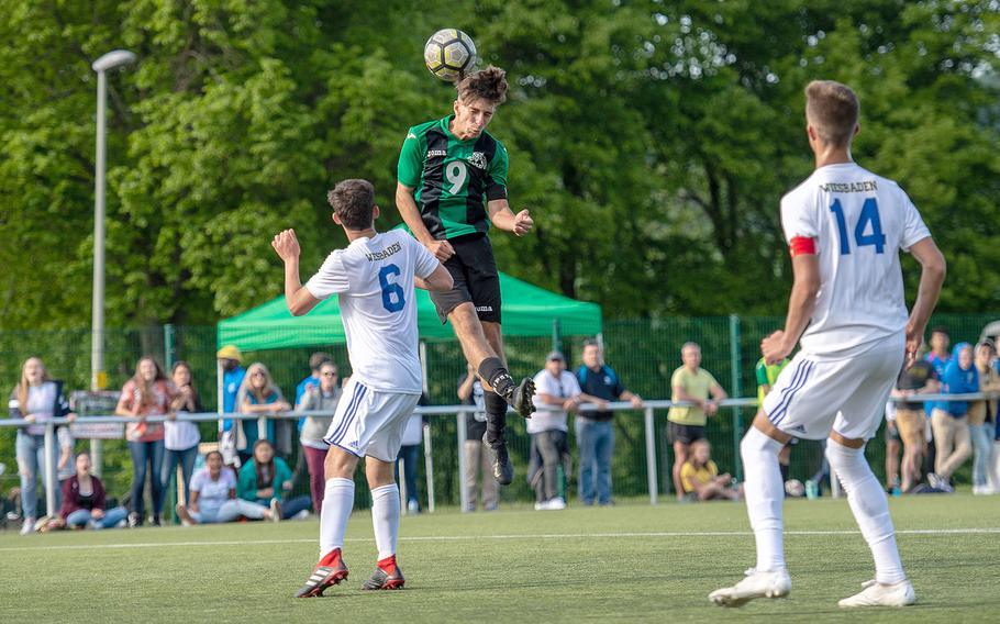 Naples' Christian Albright goes up for a header during a Division I semifinal game against Wiesbaden on the third day of the DODEA-Europe soccer championships, Wednesday, May 22, 2019.