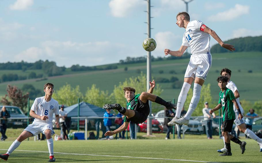 Naples' Christian Albright goes for a scissor kick on goal as Wiesbaden's Anthony Hall jumped for a header during a Division I semifinal game on the third day of the DODEA-Europe soccer championships, Wednesday, May 22, 2019.