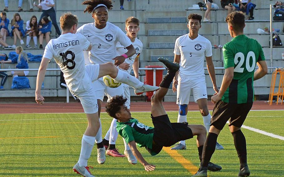 Naples' Wutthipong Khotsaeng attempts a scissors kick against Ramstein's Benjamin Brewster and Jerrell Brevard, as Gavin McMillan, Noah Yancy and Chase Traylor, from left, watch. Naples defeated Ramstein 1-0    in the boys Division I final at the DODEA-Europe championships in Kaiserslautern, Germany.