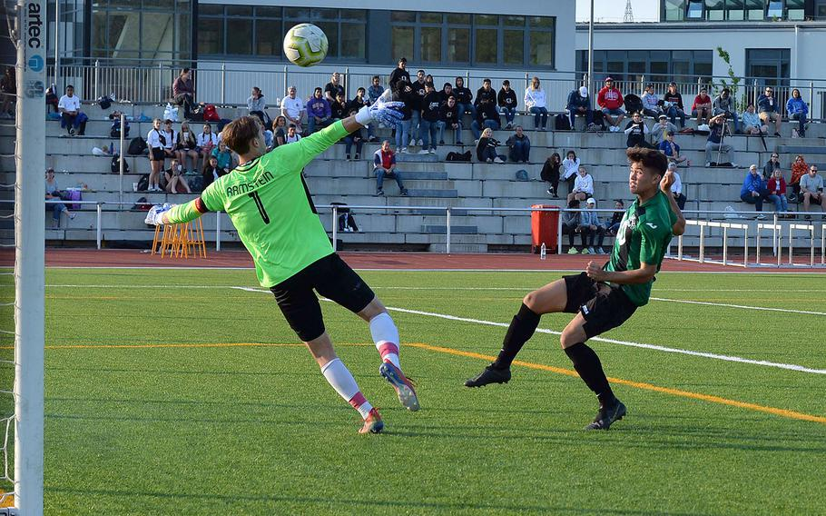 Naples' Chase Traylor watches his shot sail over Ramstein keeper Garrett Erickson for the game-winning goal in the boys Division I final at the DODEA-Europe championships in Kaiserslautern, Thursday May 23, 2019.