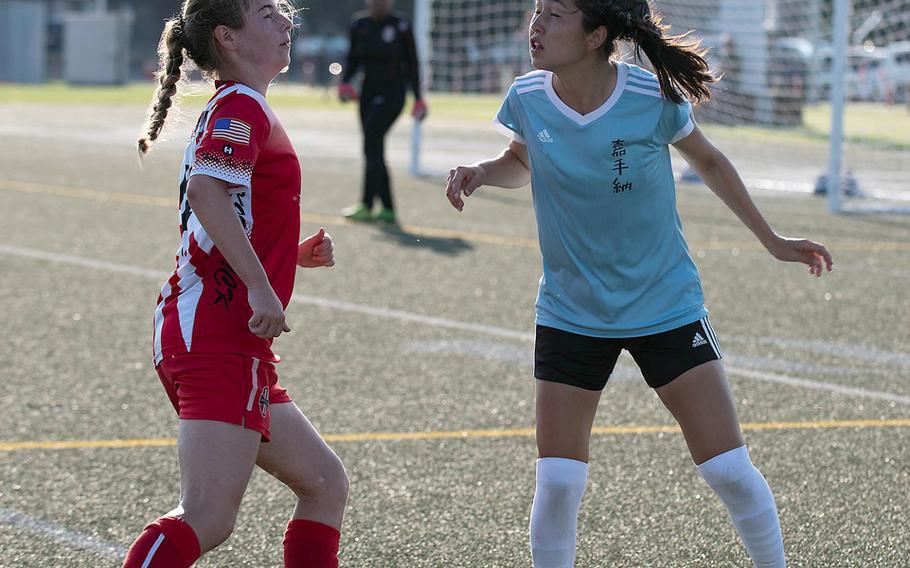 Kadena's Reina Callahan heads the ball in front of Kinnick's Lindsey Boran.