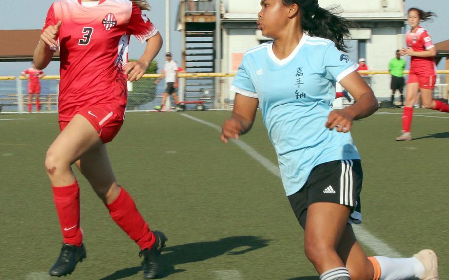Kinnick's Samantha Kenney and Kadena's Korina Radel chase down the ball.