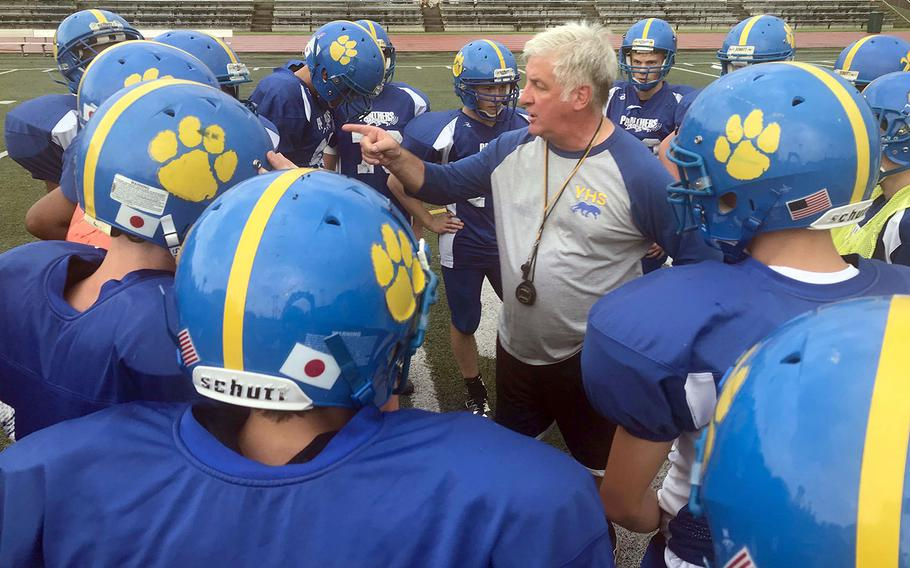 Tim Pujol, in his 21st year of coaching at Yokota, makes a point during a Panthers practice huddle.
