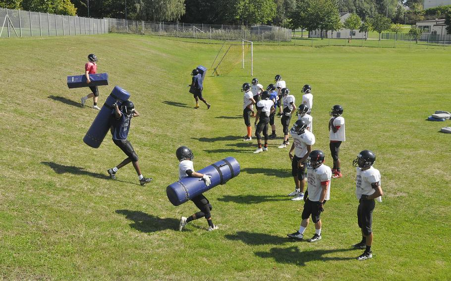 Spangdahlem Sentinels football players carry pads up and down a steep hill during a preseason practice Thursday, Aug. 22, 2019, at Spangdahlem Air Base. Where the team's practices were more specialized by position during the program's 11-man era, the smaller Sentinel roster is running more team-wide drills to prepare for the six-man game.