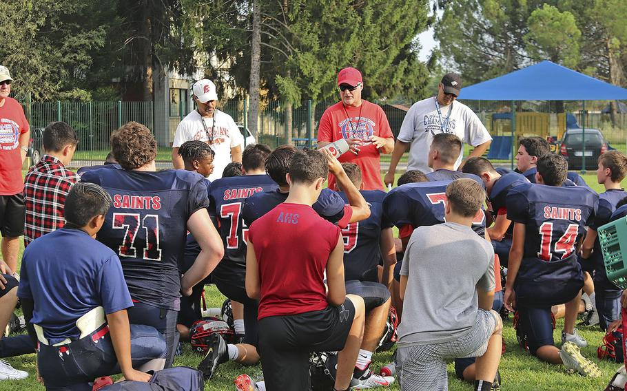 Aviano Saints football team head coach Rick Dahlstrom talks to his team following a training session in preparation for their opening game of the 2019-20 school year.