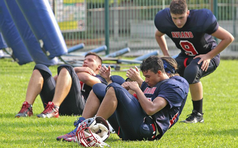 Aviano Saints football players do sit-ups as part of a training session in preparation for their opening game of the 2019-20 school year.