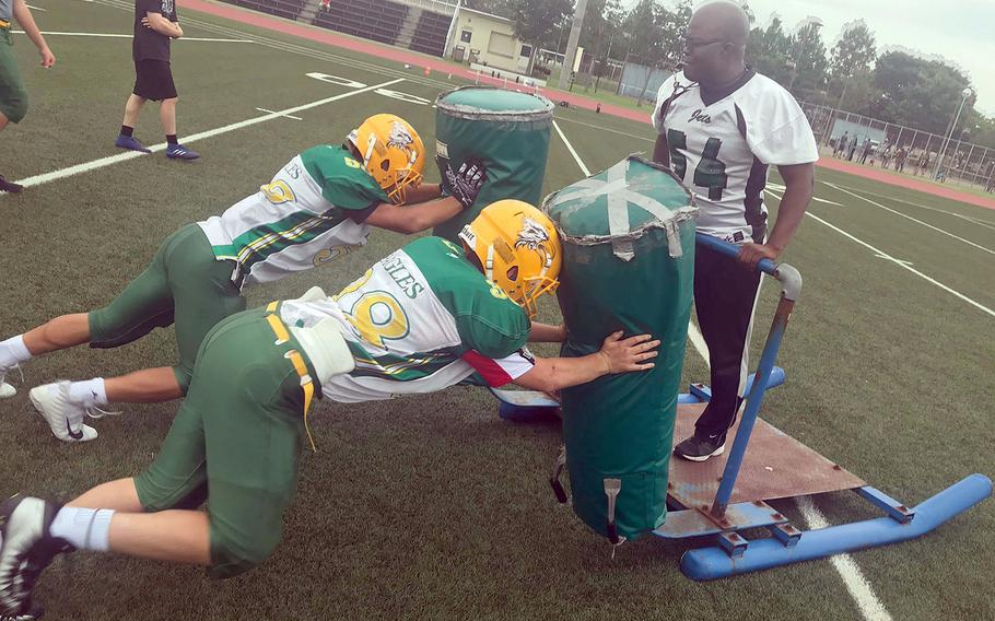 Edgren coach Jeremy Sanders works with two players on the blocking sled.