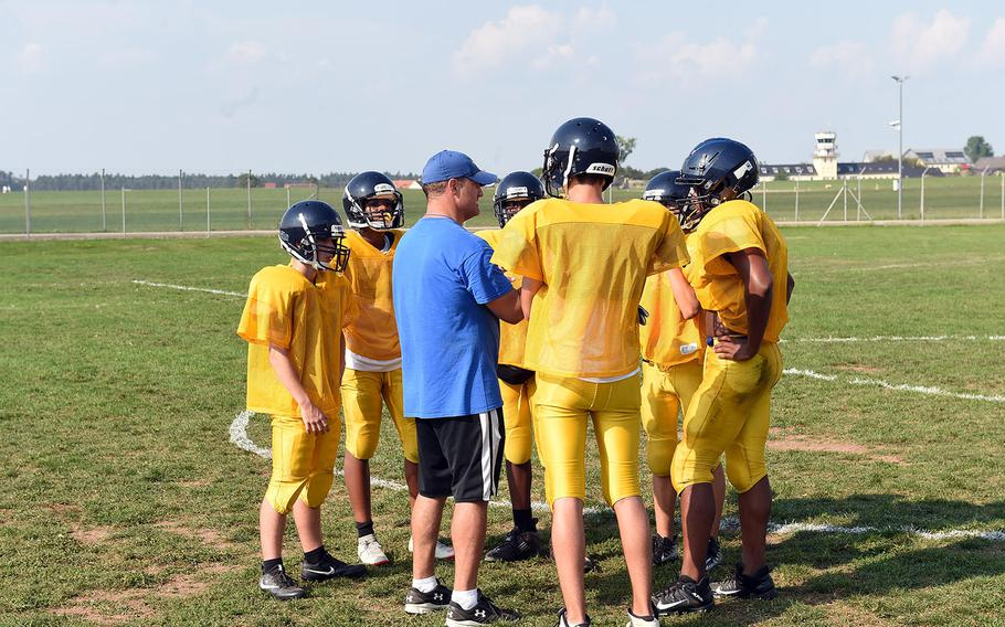 The Ansbach Cougars huddle with assistant coach Bryan Osewalt on Tuesday, Aug. 27, 2019,  at Ansbach High School.