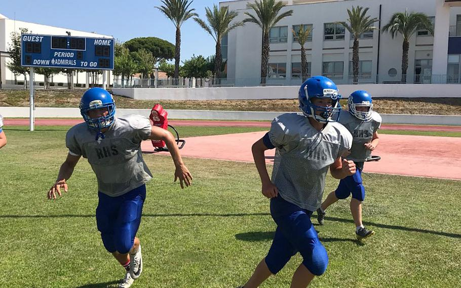 Rota football players Wes Penta, Bodie Escanes and Michael Caprio run off the field after completing a drill at a preseason practice session at Naval Station Rota, Spain.