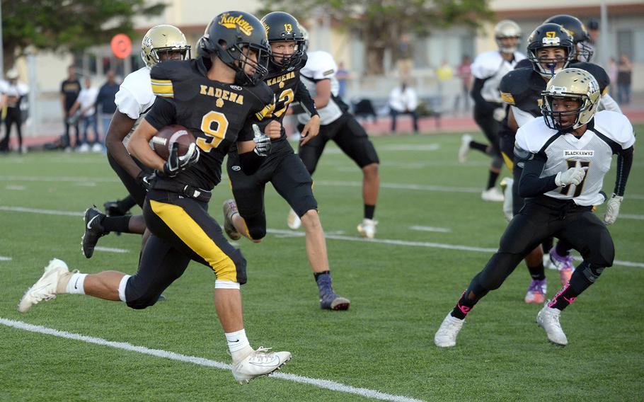 Kadena's Brandon Ray gains 13 yards on his only carry of the game, under the watchful eye of Humphreys' Jake Thomas.