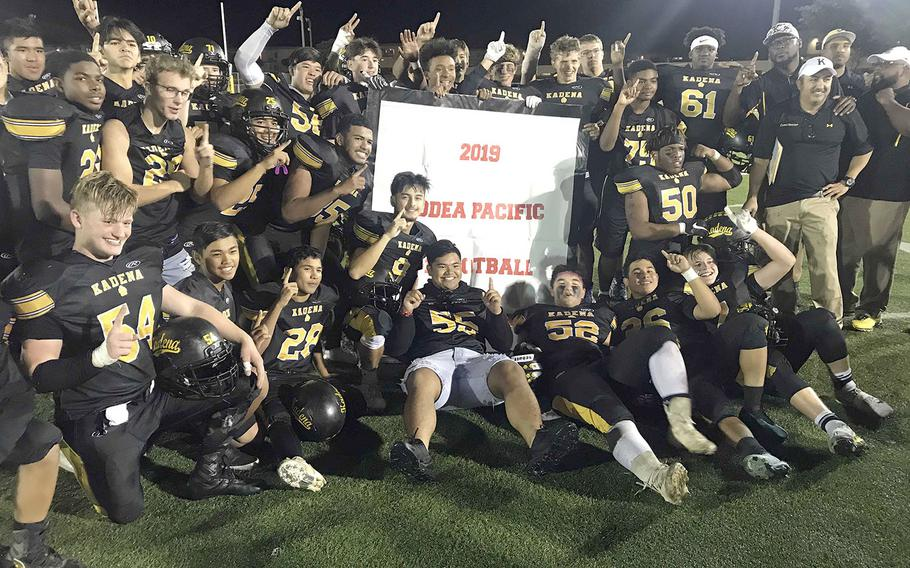 Kadena players and coaches gather round the victory banner.