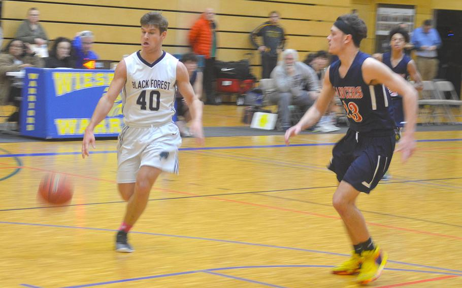 Black Forest Academy's Ruben Kuhn penetrates the Lakenheath defense during a game played at Wiesbaden High School. The Falcons beat the Lancers 76-48.