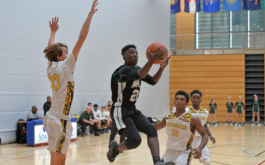 Naples' Ti Hunter aims for the basket as he splits the Vicenza defense of Trent Sayler, left, and Joseph Spencer in a Division II game at the DODEA-Europe basketball championships in Wiesbaden, Germany, Wednesday, Feb. 19, 2020. Naples won 59-55.