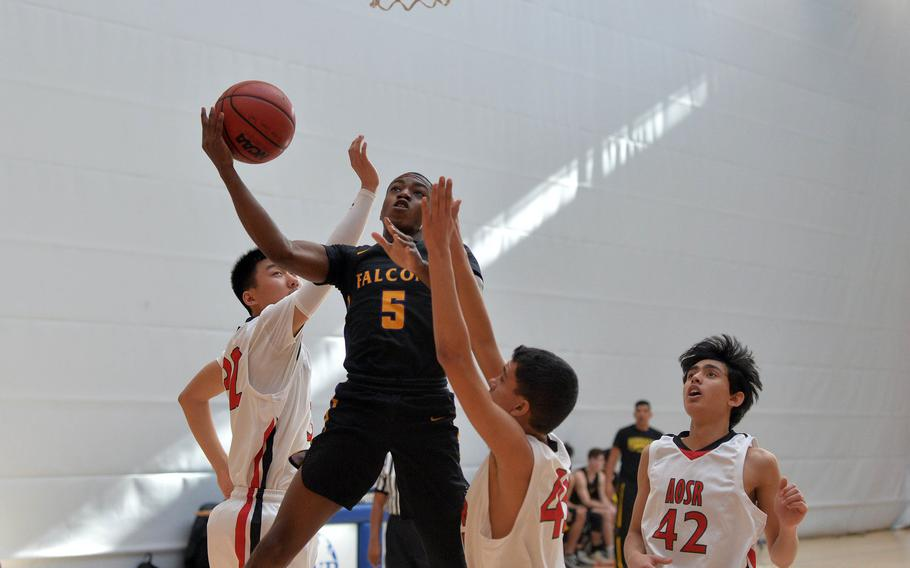 Bahrain's Cooper Lawrence gets between AOSR defenders Mengxiong Jiang, left, and William Davis for a basket in a Division II game at the DODEA-Europe basketball championships in Wiesbaden, Germany, Wednesday, Feb. 19, 2020. AOSR won 46-36.