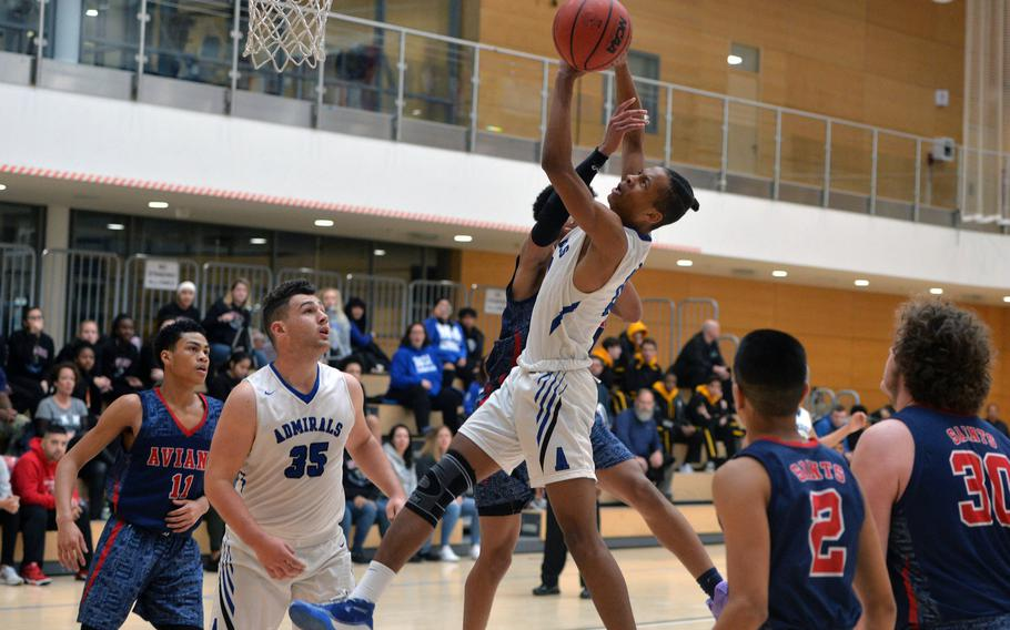 Teammates watch as Michael Tate shoots against Aviano's Malachai Brooks in a Division II game at the DODEA-Europe basketball championships in Wiesbaden, Germany, Wednesday, Feb. 19, 2020. Aviano won 48-39.