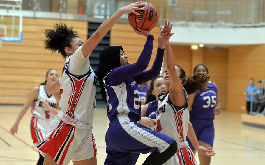 Aviano's Keyona Williams, left, and Mikyla Harkley try to stop Bahrain's Taz Abdkhair from scoring in a Division II game at the DODEA-Europe basketball championships in Wiesbaden, Germany, Wednesday, Feb. 19, 2020. Abdkhair was fouled on the play. Aviano beat Bahrain 30-12.