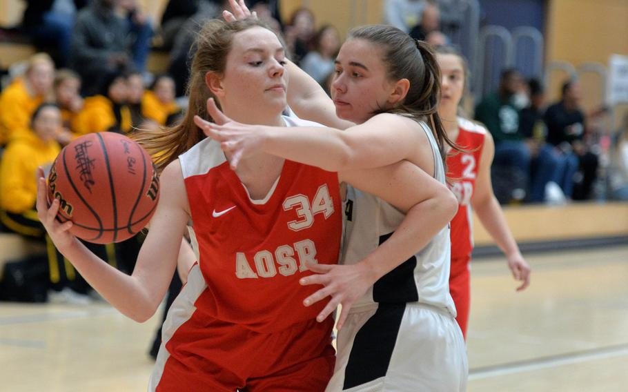 AOSR's Evan Park look for a teammate to pass to as Vicenza's Kate Hunter defends in a Division II game at the DODEA-Europe basketball championships in Wiesbaden, Germany, Wednesday, Feb. 19, 2020. Vicenza defeated AOSR 42-36.