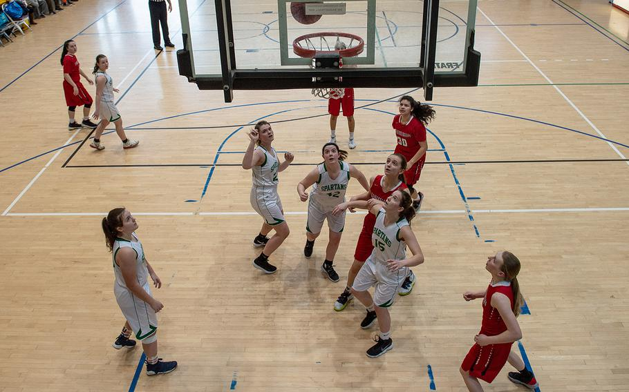 SHAPE players look up as Kaiserslautern player Audrey Elisondo's shot bounces through the hoop during the DODEA-Europe 2020 Division I basketball playoffs at the Southside gym on Ramstein Air Base, Germany, Wednesday, Feb. 19, 2020.