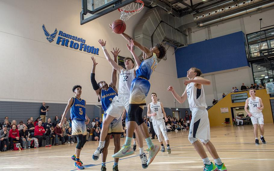 Players form Weisbaden and Black Forest Academy go up for a rebound during the DODEA-Europe 2020 Division I basketball playoffs at the Southside gym on Ramstein Air Base, Germany, Wednesday, Feb. 19, 2020.