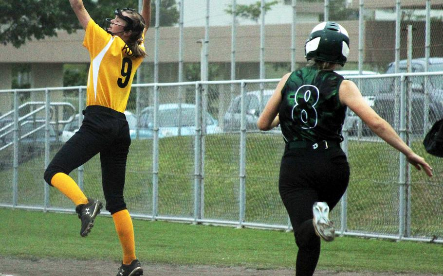 Kadena first baseman Daisylynn Efraimson reaches up for the ball as Kubasaki baserunner Kristen Lininger races to the bag during Wednesday's Okinawa softball game. Lininger was called out on the play.The Dragons won 6-2.