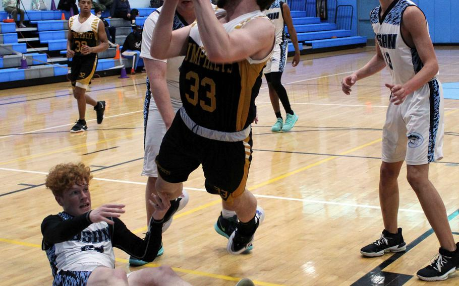Humphreys Gold's Christopher Brown loses his footing as he puts up a shot between Osan American Blue's Martin Walker and Brandon Edmunds during Thursday's Korea boys basketeball game. Blackhawks Gold won 64-44.