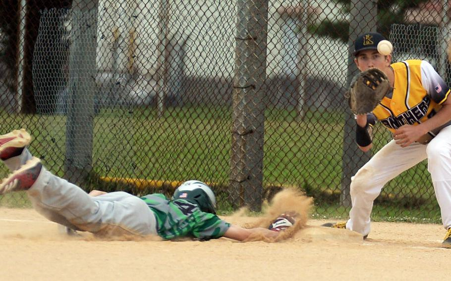 Kubasaki's Andrew Welte dives back into first base ahead of the pickoff throw to Kadena's Wyatt Boerigter during Thursday's Okinawa baseball game. The Panthers won 10-6.