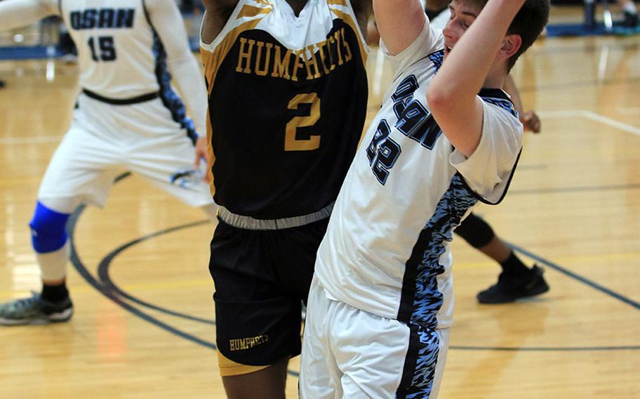 Osan American Black's Matthew Cornelius gets hemmed in by Humphreys Black's Myles Johnson during Thursday's Korea boys basketball game. Blackhawks Black won 71-42.