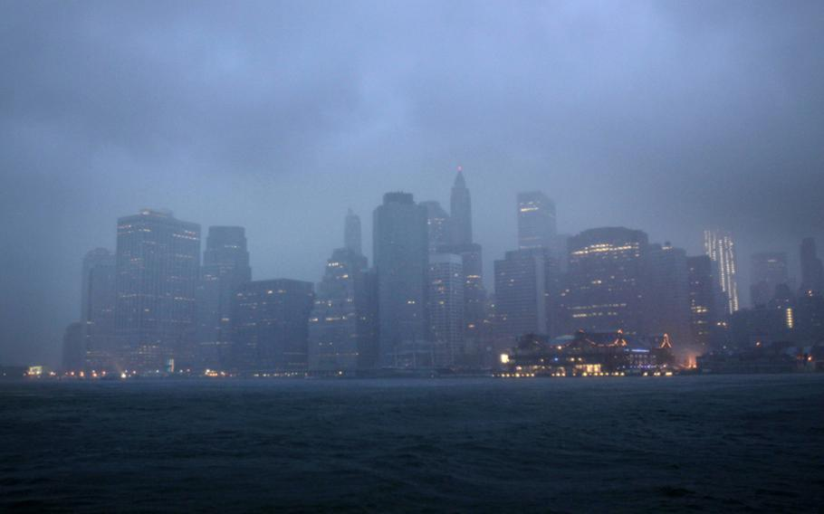 Lower Manhattan is seen amidst dark clouds in New York on Sunday as Hurricane Irene bore down, bringing winds and rapidly rising seawater that threatened parts of the city. The rumble of the subway system was silenced for the first time in years, the city all but shut down for the strongest tropical lashing since the 1980s.