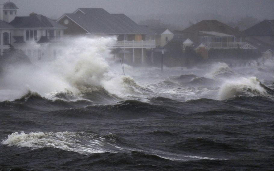 Waves crash over the shore during high tide Sunday during a storm surge from Hurricane Irene in Bayshore, N.Y., on Long Island.
