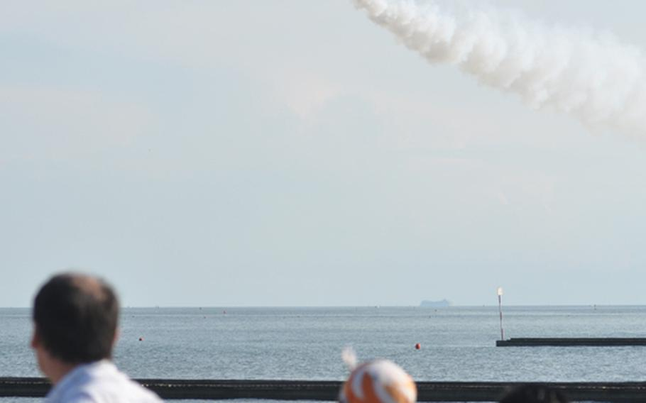 Italian onlookers watch a jet perform in an air show over the Adriatic Sea off the coast of Jesolo, Italy, earlier this summer.