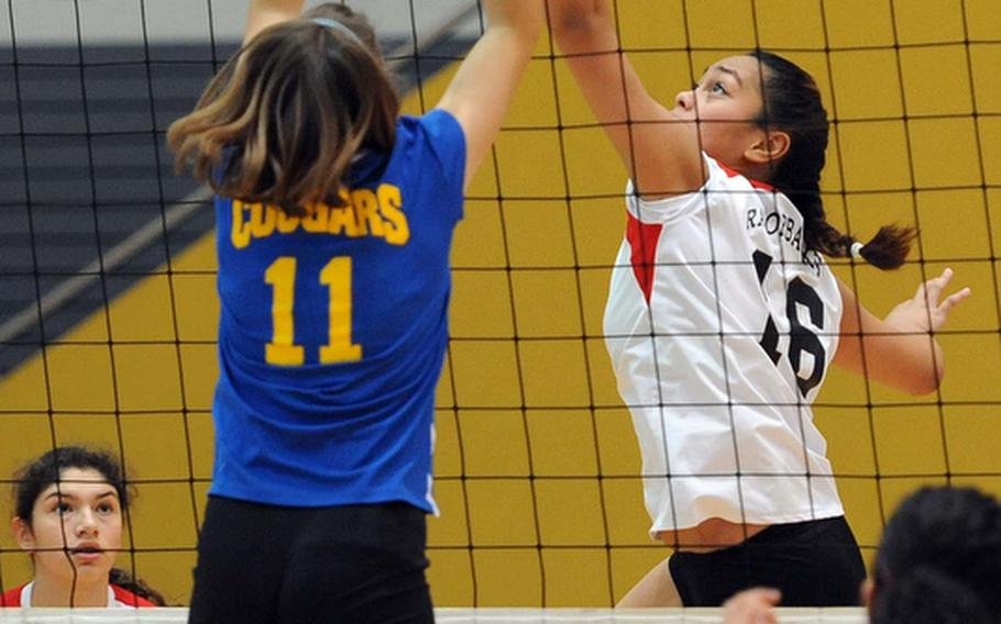 Schweinfurt's Maria Maika gets the ball over the outstretched hands of Ansbach's Duplessie Lauren in a Division II match at the DODDS-Europe volleyball championships. Ansbach won the match 25-22, 25-9.