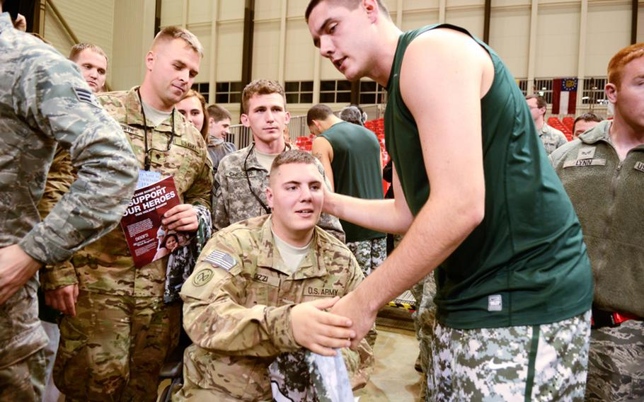 U.S. Army Spc. Cory Gizzi, a wounded warrior with the 27th Maintenance Brigade, receives a jersey from Michigan State's Kenny Kaminski Friday night after Connecticut upset Michigan State in the Armed Forces Classic at Ramstein Air Base, Germany.