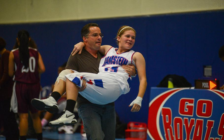 Ramstein High School's Dominique Dubois is carried to her team's bench by her father, David Dubois, Friday night as her team defeated Vilseck High School at Ramstein Air Base.
