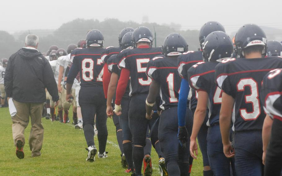 Bitburg coach Mike Laue leads his team across the field to shake hands with defeated Baumholder on Saturday at Bitburg, Germany. Bitburg won the game 42-6 and set a new DODDS-Europe record with its 32nd consecutive victory.