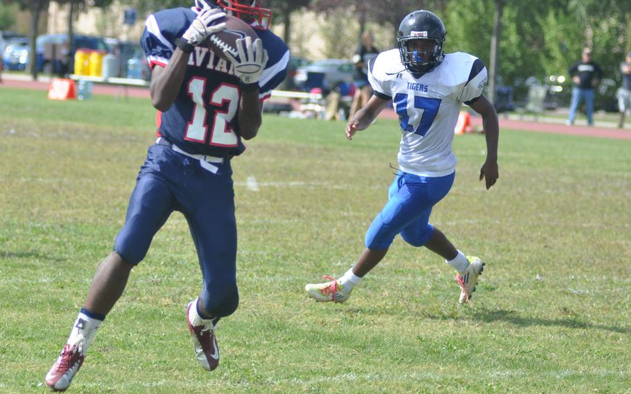 Aviano's Jamal Thomas catches a pass as Hohenfels' AJ Day looks on during a game Saturday at Aviano Air Base, Italy. Thomas had 11 grabs for 97 yards,  including a touchdown . Hohenfels won 41-24.