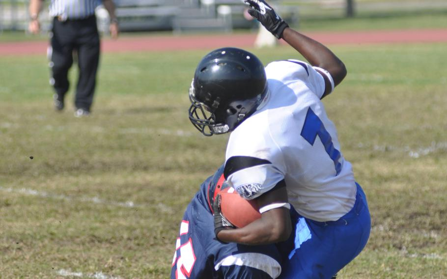 Hohenfels' Marcus Dudley Jr. gets wrapped up by Aviano's Te'Kevin Boston during Saturday's game at Aviano Air Base, Italy. Dudley ran 45 yards and scored a touchdown off an interception assisting in Hohenfels' 41-22 win.