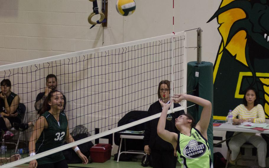 Alconbury senior Leila Hall sends a reverse-lob to SHAPE defenders Saturday, during a girls volleyball match at RAF Alconbury, England. Alconbury added to its winning season by defeating SHAPE in three straight matches, 25-6, 25-23, 25-8.